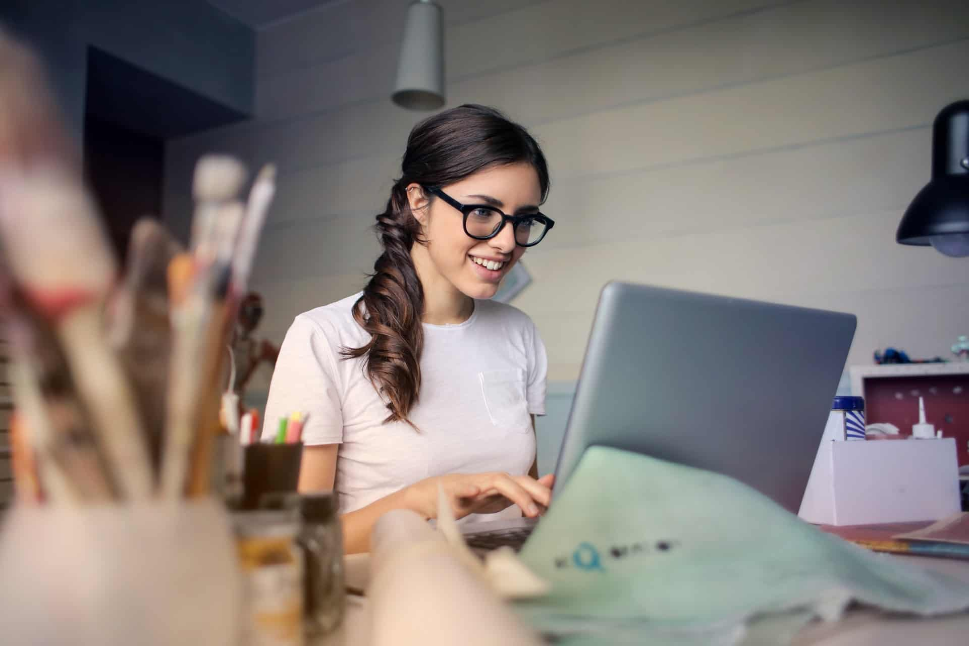 Young Woman in glasses on laptop smiling